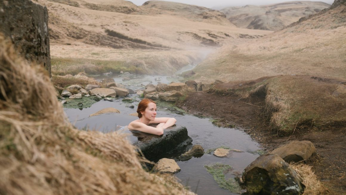 woman sitting in pond near sandy hills in foggy weather
